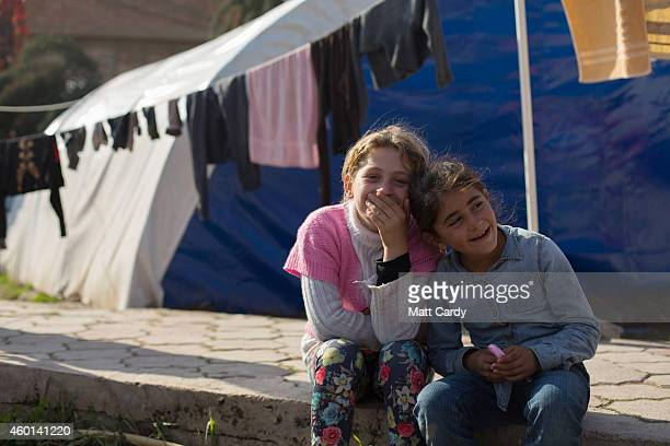 Iraqi Christian children sit in front of tents erected in the grounds of Mar Elias Catholic Church in Ankawa that has now become home to hundreds of...
