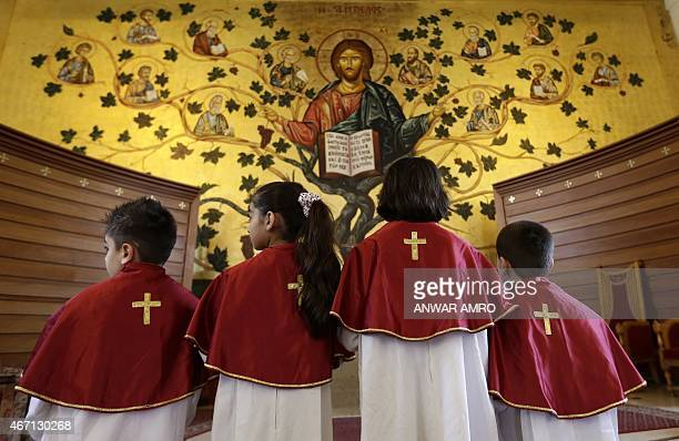 Iraqi Christian children who fled the violence in the Nineveh province attend a mass with their mothers at a chuch in Dekwaneh east of the Lebanese...
