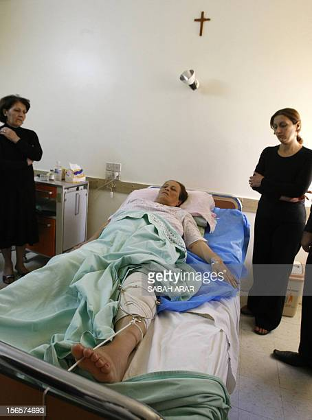 Iraqi Christian Siba Nadhir who survived last week's church carnage in Baghdad lies on her hospital bed surrounded by mourning family members in...