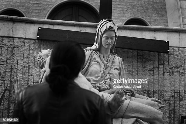 Iraqi Christian woman prays in front of a statue of Merry February 2 in a church in the district of Jaramana on the edge of Syrian capital Damascus...