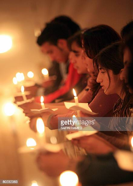 Iraqi Christians hold candles as they attend a mass dedicated to Chaldean Catholic Archbishop of Mosul Paulos Faraj Rahho at a church in the Kurdish...