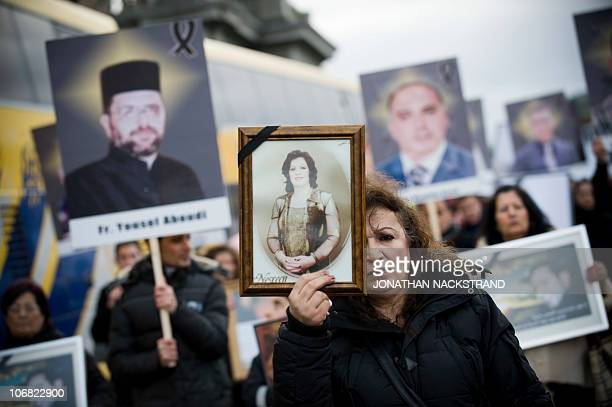 Iraqi Christians hold on November 14 2010 in Stockholm pictures of some of the 53 people who were killed on October 31 in attack at the main Syriac...