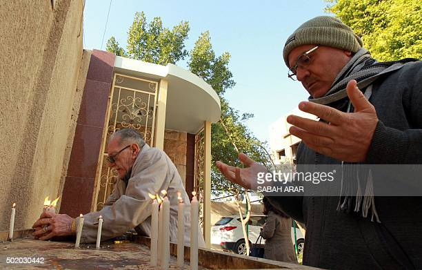 Iraqi Christians light candles and pray at the Virgin Mary Chaldean church in the Karrada neighborhood of the Iraqi capital Baghdad on December 20 as...