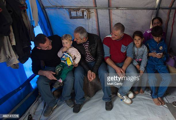 Iraqi Christians sit in their tent erected in the grounds of Mar Elias Catholic Church in Ankawa that has now become home to hundreds of Iraqi...