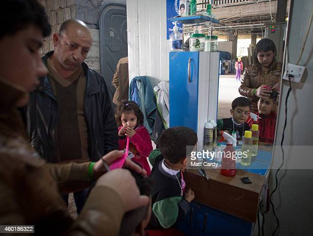 Iraqi Christians who fled from their homes because of Islamic State's advance earlier this year operate a barbers shop inside the entrance hall of...
