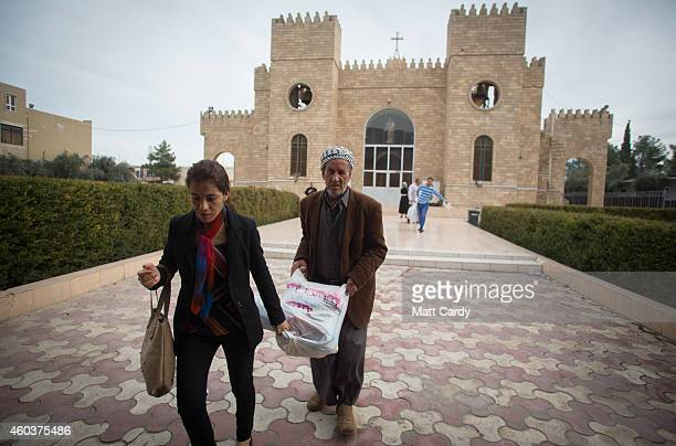 Iraqi Christians who fled from their homes because of Islamic State's advance earlier this year receive a food parcel from a aid organisation...