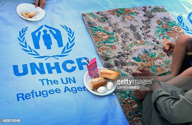 ASSIR Iraqi Christians who fled with their families the violence in Iraq's largest Christian town of Qaraqosh eat sitting on an UNHCR tarpaulin in...