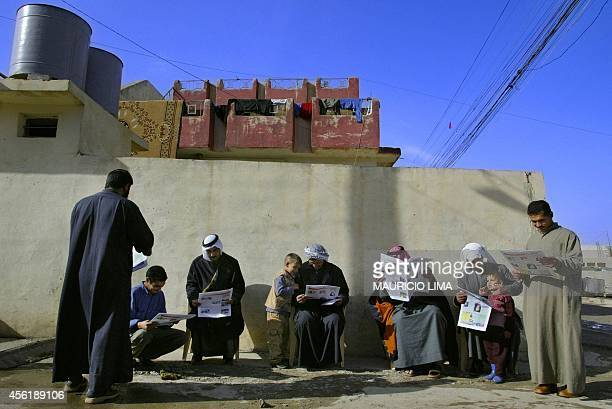 Iraqi citizens read an election information flyer given out by US and Iraqi soldiers during a patrol next to a polling station in the restive...