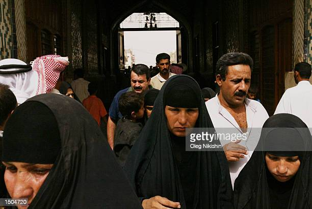 Iraqi citizens walk inside a mosque named the Shrine of the Imam Ali Ibn Abi Talib October 18, 2002 in the town known as Najaf, which is...