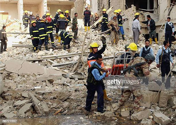 Iraqi civil defense carry a body from the collapsed building where two suicide car bombs exploded near an Interior Ministry building causing some...