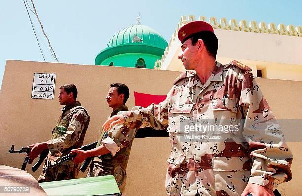 Iraqi Civil Defense Corps members guard a street corner May 1 2004 in the flashpoint city of Fallujah Iraq An 1100 member force Iraqi security force...