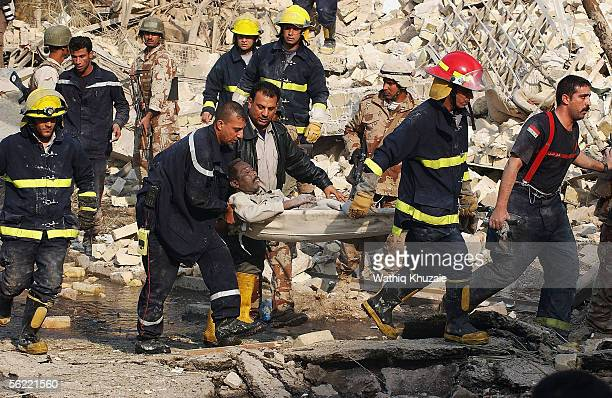Iraqi civil defense rescue an Iraqi man from the collapsed building where two suicide car bombs exploded near an Interior Ministry building causing...