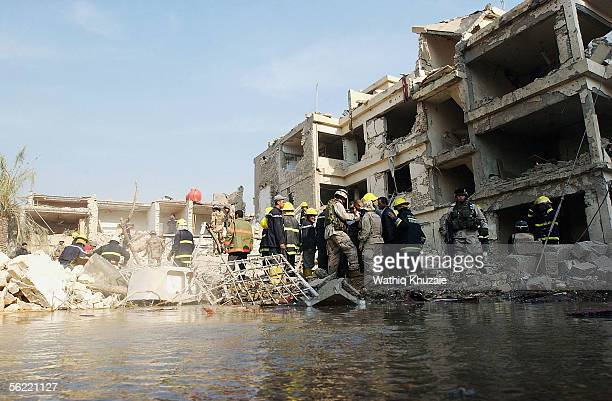 Iraqi Civil Defense workers and US soldiers attempt to remove debris to allow them to rescue any survivors at the area where two suicide car bombs...