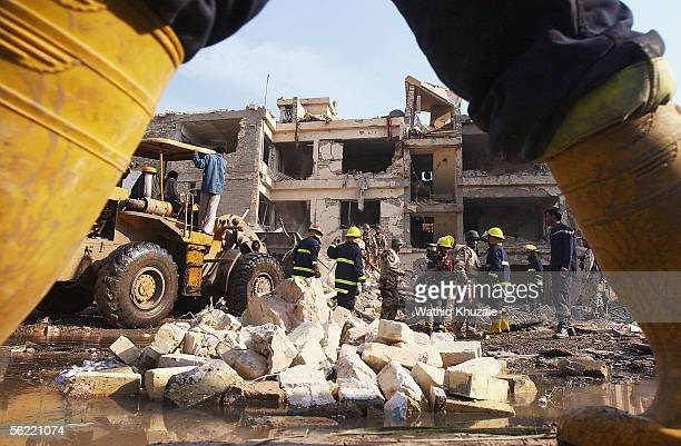 Iraqi Civil Defense workers attempt to remove debris to allow them to rescue any survivors at the area where two suicide car bombs exploded near an...