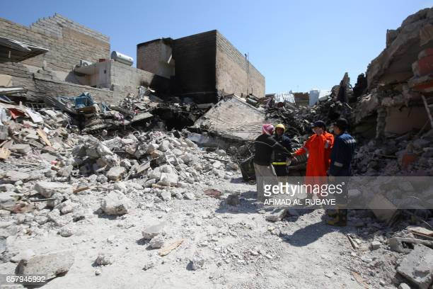 Iraqi civilians and rescue workers inspect the damage in the Mosul alJadida area on March 26 following air strikes in which civilians have been...