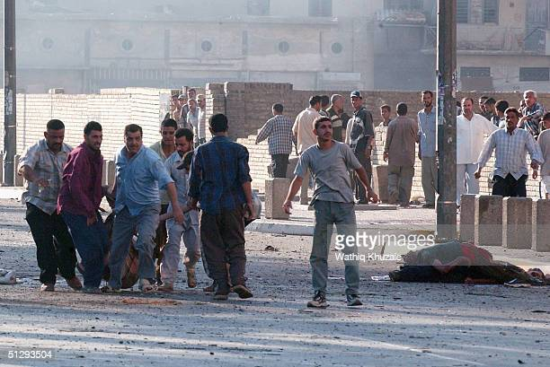 Iraqi civilians carry an injured man after clashes on September 12 2004 in Haifa Street Baghdad Iraq Fighting broke out in the early hours of...