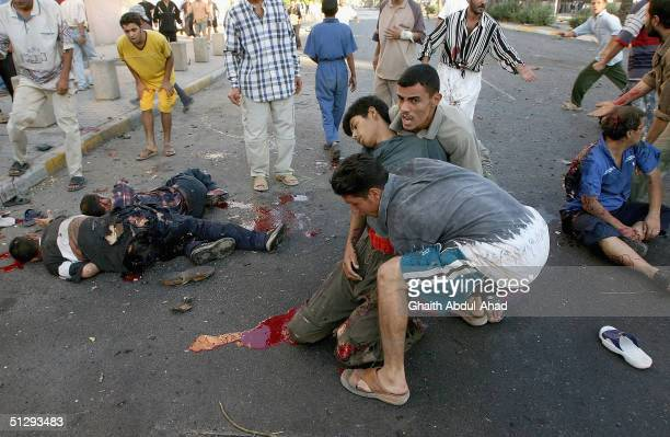 Iraqi civilians carry an injured man as other dead and injured people lie in the street on September 12 2004 in Haifa Street Baghdad Iraq Fighting...