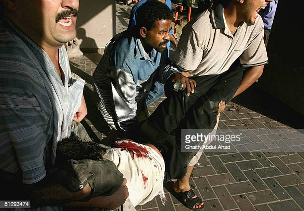 Iraqi civilians carry an injured man during fighting on September 12 2004 in Haifa Street Baghdad Iraq Fighting broke out in the early hours of...