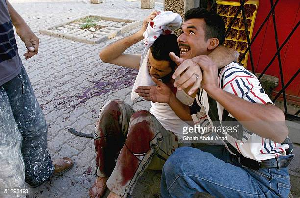 Iraqi civilians carry an injured man on September 12 2004 in Haifa Street Baghdad Iraq Fighting broke out in the early hours of September 12 2004 as...