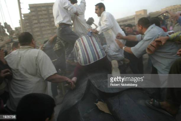 Iraqi civilians destroy a Saddam Hussein statue after toppling it with help from U.S. Marines from the Marine 1st Division near the Palestine Hotel...