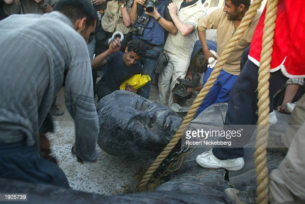 Iraqi civilians destroy a Saddam Hussein statue after toppling it with help from US Marines from the Marine 1st Division near the Palestine Hotel...