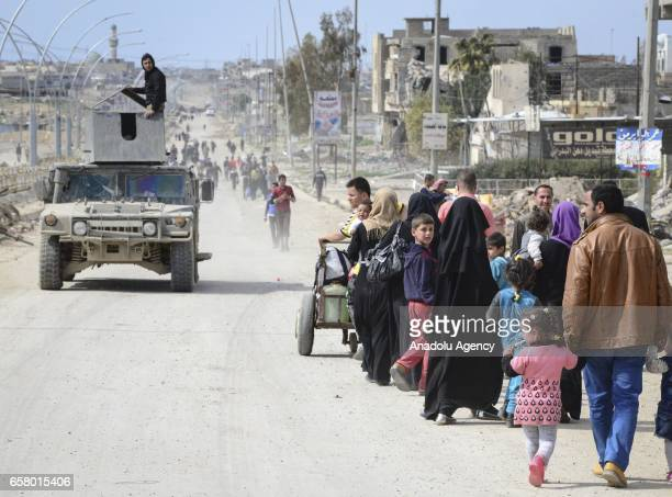 Iraqi civilians, fled from clashes between Iraqi Army and Daesh terrorists, leave with their belongings from Tal al-Rumman neighborhood to take...