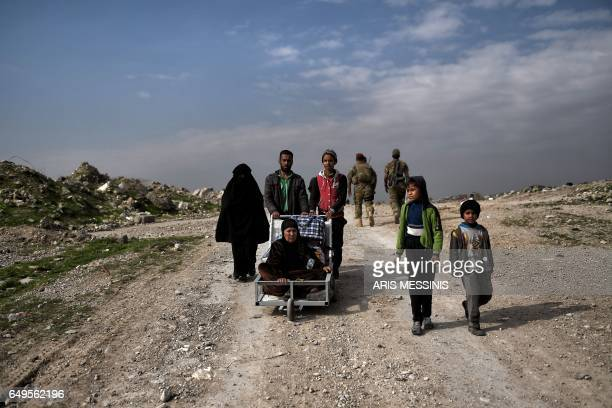 Iraqi civilians flee Mosul as Iraqi forces advance inside the city during fighting against Islamic State group's fighters on March 8 2017 Supported...