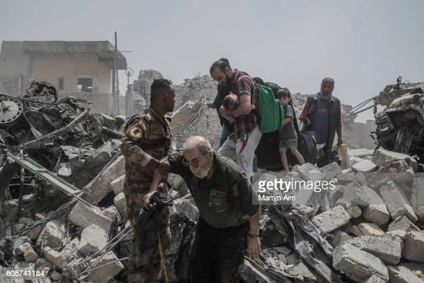 Iraqi civilians flee the Old City district where heavy fighting continues on July 2 2017 in Mosul Iraq Iraqi forces continue to encounter stiff...