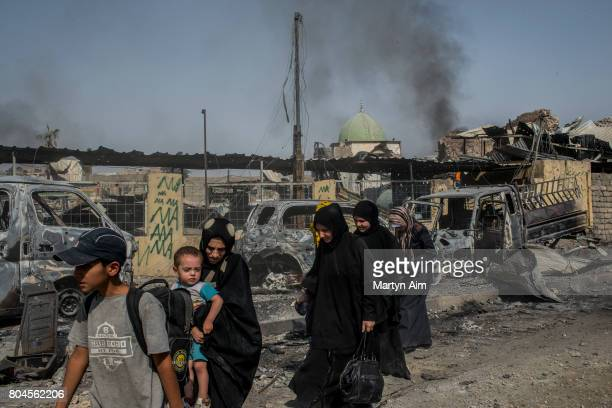 Iraqi civilians flee through the Old City of west Mosul in front of the destroyed alNuri mosque where heavy fighting continues on June 30 2017 in...