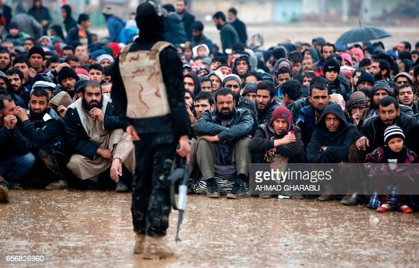 TOPSHOT Iraqi civilians fleeing the city of Mosul sit under the rain on March 23 2017 as Iraqi forces advance in their massive operation to retake...