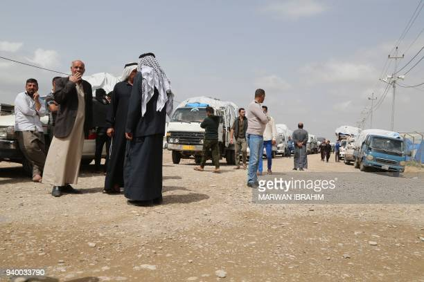 Iraqi civilians from the Hawija region who were displaced by fighting with Islamic State group fighters stand by governmenthired trucks waiting to...