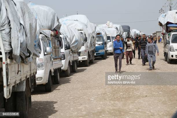 Iraqi civilians from the Hawija region who were displaced by fighting with Islamic State group fighters walk past governmenthired trucks waiting to...