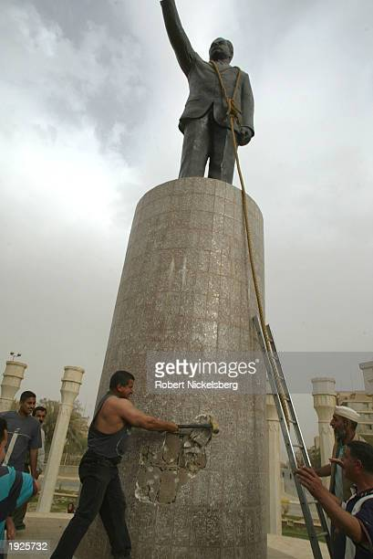 Iraqi civilians prepare to topple a Saddam Hussein statue with help from US Marines from the Marine 1st Division near the Palestine Hotel April 9...