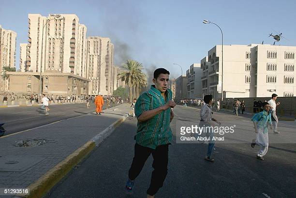 Iraqi civilians runaway after US helicopters opened fire on September 12 2004 in Haifa Street Baghdad Iraq Fighting broke out in the early hours of...