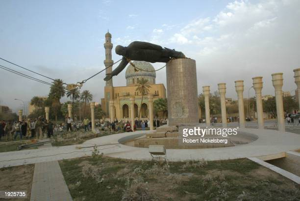 Iraqi civilians take down a Saddam Hussein statue with help from US Marines from the Marine 1st Division near the Palestine Hotel April 9 2003 in...