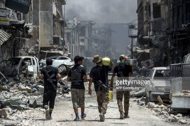 TOPSHOT Iraqi CounterTerrorism Services members carry food as they walk in the Old City of Mosul on July 3 2017 during an ongoing offensive to retake...