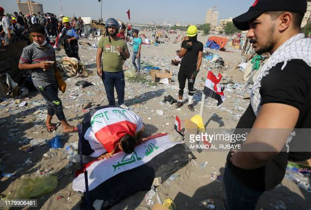 TOPSHOT Iraqi demonstrators build symbolic tombs for those who were killed during ongoing antigovernment protests near alJumhuriya bridge which leads...