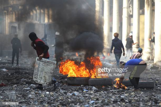 Iraqi demonstrators burn tyres amid clashes with security forces in the capital Baghdad's alRasheed street near alAhrar bridge on November 27 during...