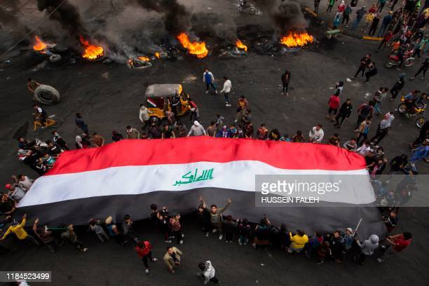 Iraqi demonstrators carry a giant national flag as others burn tyres to cut-off roads in the southern city of Basra on November 25, 2019.