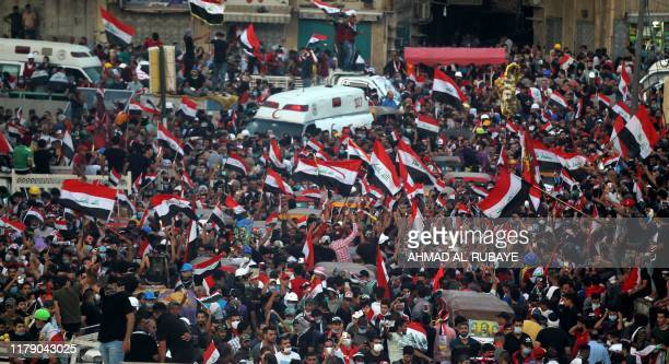 Iraqi demonstrators chant slogans and wave their country's national flags during ongoing anti-government demonstrations at Tahrir Square in the...