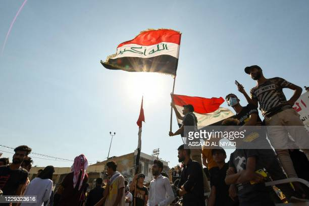 Iraqi demonstrators chant slogans during a gathering in Haboubi Square in the southern city of Nasiriyah on October 28 to demand a total overhaul of...