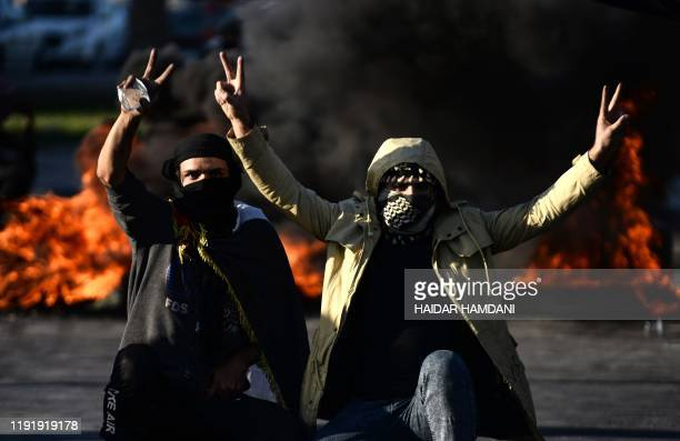 Iraqi demonstrators flash the victory sign next to burning tyres as angry protesters blocked roads in the central shrine city of Najaf on January 5...