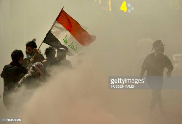 Iraqi demonstrators gather amid smoke after fire services extinguished fire on tires during a protest near the governor's residence in the southern...
