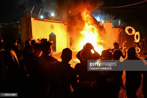 Iraqi demonstrators gather as flames start consuming Iran's consulate in the southern Iraqi Shiite holy city of Najaf on November 27 two months into...