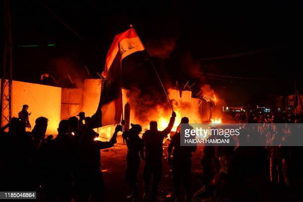TOPSHOT Iraqi demonstrators gather as flames start consuming Iran's consulate in the southern Iraqi Shiite holy city of Najaf on November 27 two...