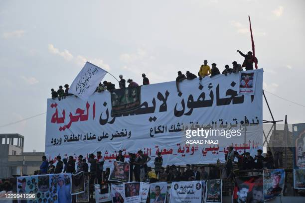 """Iraqi demonstrators gather beneath a banner which reads """"the fearful cannot bring about freedom"""" in Habboubi square, in the southern city of..."""