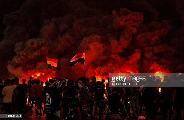Iraqi demonstrators gather near burning tires during a protest near the governor's residence in the southern city of Basra, to protest assassinations...