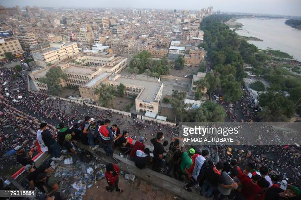 Iraqi demonstrators gather on several storeys of the Turkish restaurant an abandoned building in the capital Baghdad overlooking the Tahrir square...