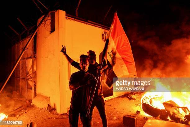 TOPSHOT Iraqi demonstrators gesture as flames start consuming Iran's consulate in the southern Iraqi Shiite holy city of Najaf on November 27 two...