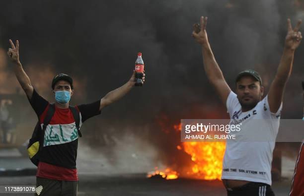 Iraqi demonstrators gesture next to a tyre fire during a demonstration against state corruption failing public services and unemployment in the Iraqi...